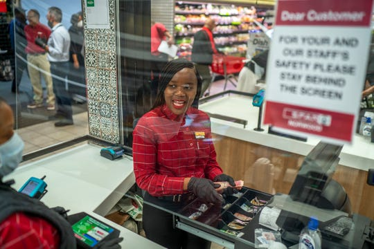 In this March 30, 2020, photo, Zandile Mlotshwa, 21, cashier at Spar supermarket in the Norwood suburb of Johannesburg, South Africa, counts her cash at the end of her shift.