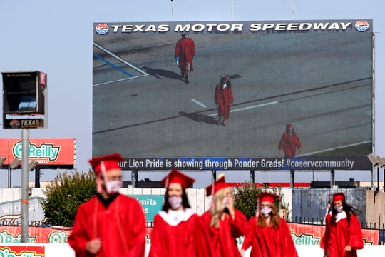 The large television screen in the infield of the track shows Ponder High School graduates walking onto the front stretch of the track to participate in their graduation ceremony at Texas Motor Speedway in Fort Worth, Texas, Tuesday, May 19, 2020.