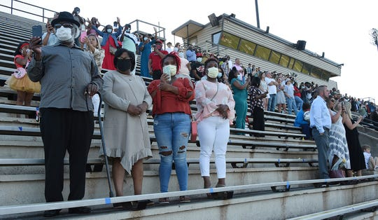 In this Monday, May 12, 2020 photo, families wore masks and practice social distancing during Central High School's first of five live graduation ceremonies at Garrett-Harrison Stadium in in Phenix City, Ala.