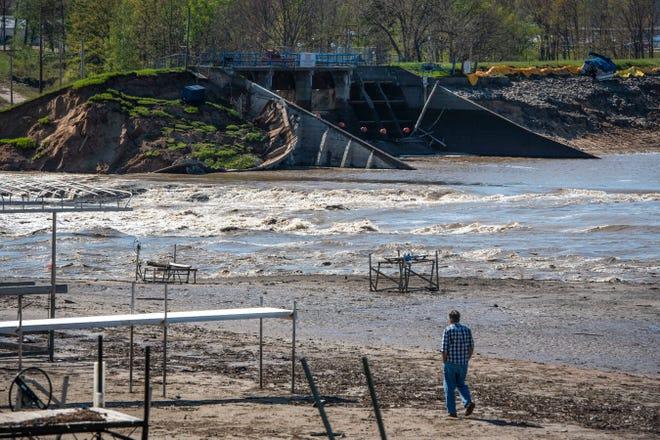 Seorang pria berjalan menuju Bendungan Edenville di Danau Wixom di Beaverton setelah tanggulnya pecah.
