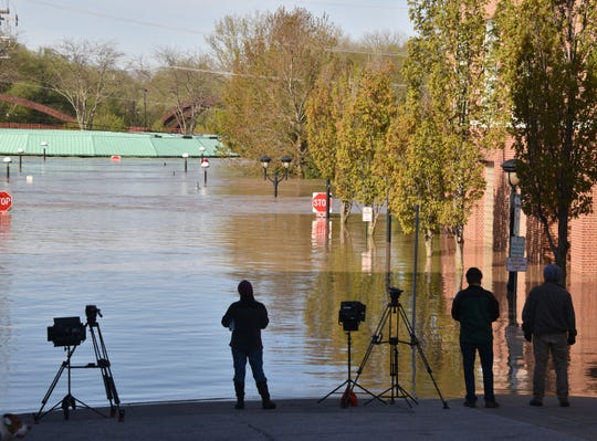 Television crews watch the Tittabawassee River rise in downtown Midland to an estimated 10 feet over flood stage on May 20.