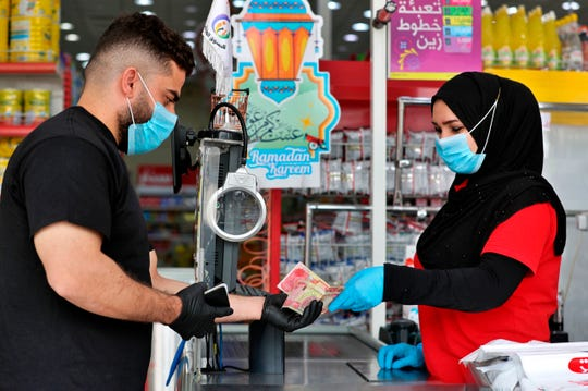 In this May, 2, 2020, photo, a man uses banknotes to pay for his purchases at the mall in Basra, Iraq.