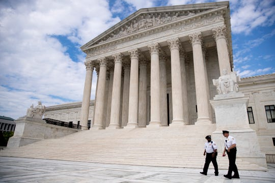 Security officers, one wearing a mask, walk in front of the Supreme Court, Thursday, May 14, 2020, in Washington.