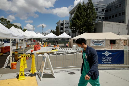 A healthcare worker walks past a COVID-19 test site on Tuesday, May 19, 2020, at Santa Clara Valley Medical Center in San Jose, Calif.