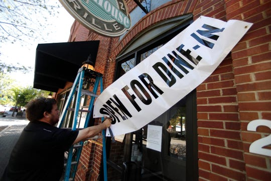 In this April 27, 2020, file photo, Jason Godbey hangs a banner over the entrance of Madison Chop House Grille as they prepare to shift from take out only to dine-in service in Madison, Ga.
