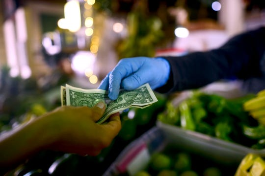 In this March 19, 2020, file photo, Jorge Otero, owner of a fruit and vegetables stand, wears gloves as he exchanges cash with a customer, during a government curfew aimed at curbing cases of the new coronavirus in San Juan, Puerto Rico.