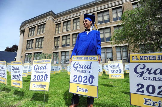 E. L. Meyers High School graduate Jose Sepulveda poses for family pictures while holding his graduation yard sign after picking it out from the others that were placed in front of the school, Tuesday May 19, 2020, in Wilkes-Barre, Pa., where the class of 2020 held a Virtual Graduation Ceremony.