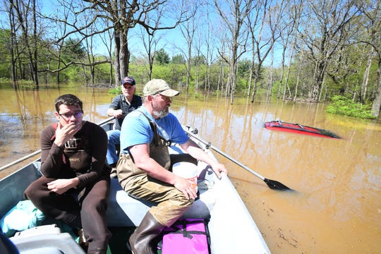"Don Thomas (background) rows Nick Maki and son Jason Thomas past Jason's red 2001 Grand Cherokee, barely visible above the flooding, after picking up Jason's two family cats from his flooded home near W. Signet in Midland.  Jason Thomas, ""We walked out last night, me, my wife and three kids.""  ""Other than the pictures put up high or upstairs, everything else is gone."""