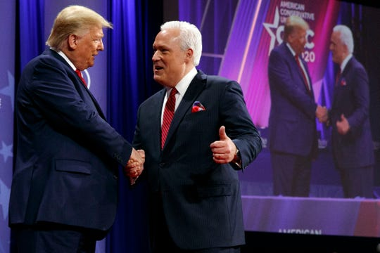 In this Feb. 29, 2020, file photo, President Donald Trump is greeted by Matt Schlapp, Chairman of the American Conservative Union, as the president arrives to speak at the Conservative Political Action Conference,  at National Harbor, in Oxon Hill, Md.