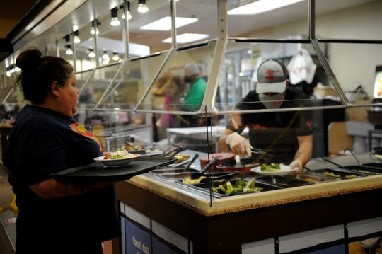 An employee at the Evansville Golden Corral serves a diner cafeteria-style behind a Plexiglas shield on Monday, May 18, 2020.
