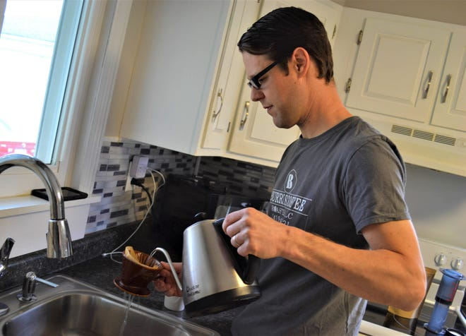 Daniel Burris brews a cup of Burris Coffee Roasters coffee using the pour over method.