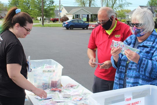 Christopher and Michele Wood, at right, look through cloth masks Wednesday at the Clyde VFW 3343 parking lot. The VFW's Ladies Auxiliary held a free mask giveaway, with residents asked to bring a nonperishable food donation in exchange for a mask.