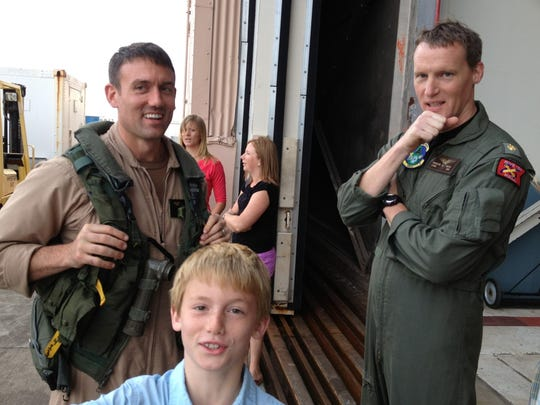 U.S. Navy Cmdr. Jamie Delcore is joined by one of his sons, Zane, and Andrew Wiese, an officer in his squadron, as he returns from a deployment. The New Franken native and Luxemburg-Casco High School graduate will take command of Tactical Air Squadron 11 on June 3.
