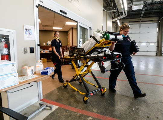 EMTs Heather Barrett, left, and Christina Wood  return to their ambulance after delivering a patient to the emergency room, recently.