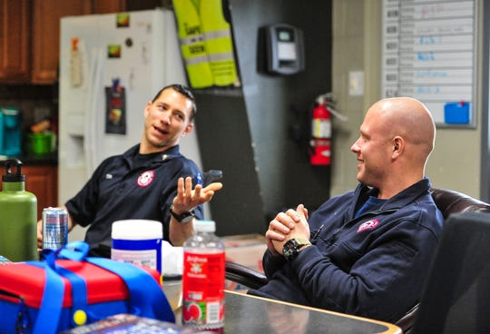 Great Falls Emergency Services EMT's Jason Edie, right, and Tim Egnoski socialize with their colleagues as they wait for emergency pages in the crew quarters, recently.