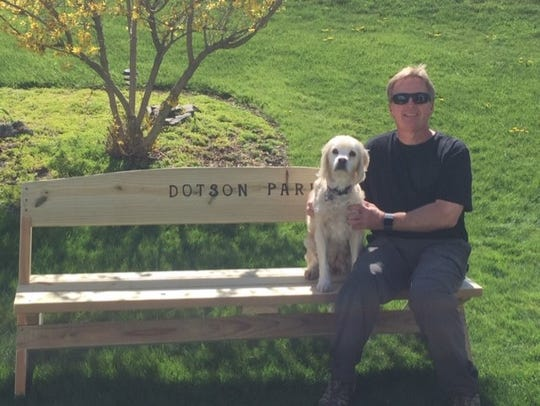 Peter Farley and his dog, Lucy, sit on one of the two benches he made for Danby's Dotson Park.