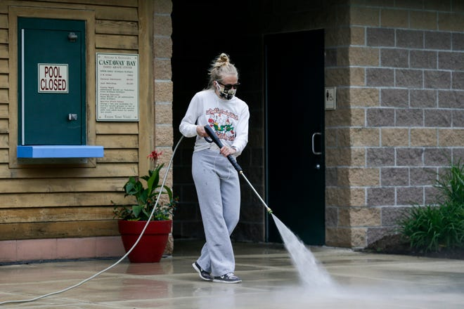 Emily Norris power washes the entrance to Castaway Bay in Armstrong Park, Wednesday, May 20, 2020 in Lafayette.