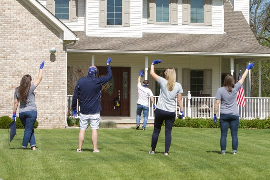 Having just placed a bag containing cap and gown on the doorknob of a senior's home, Hartland High School faculty wave as the sound of celebratory honks comes from the bus transporting the staff from home to home for these deliveries Wednesday, May 20, 2020.