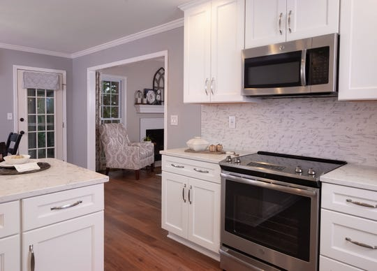 Stainless steel appliances, the existing light grey walls, and white and grey patterned window treatments complete the home's new, lightened look in this Lyndon home.