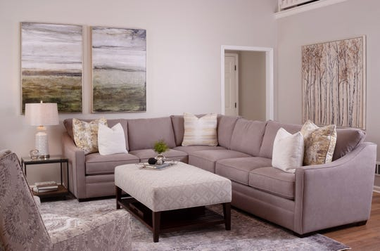 A gray sectional with performance fabric sits upon a muted, multi-colored rug in the living room in this Lyndon home.