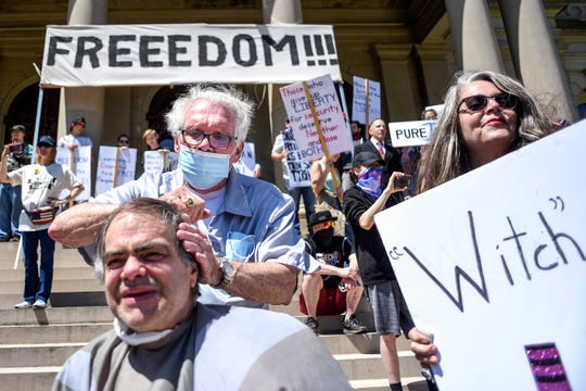 "Owosso barber Karl Manke, center, cuts the hair of Scott Farrand, of Lansing, during the ""Operation Haircut"" protest on Wednesday, May 20, 2020, at the Michigan State Capitol in Lansing. The event, organized by the Michigan Conservative Coalition, was held in opposition to Gov. Gretchen Whitmer's stay home order that closed hair salons and barbershops during the coronavirus pandemic."