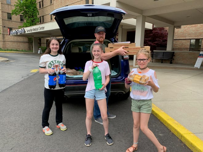 Mallory, 13, Addie, 11, and Spencer, 8, and dad Robin Shields, delivered pizzas and more to three area hospitals' ER staffs this past weekend, money earned from the girls' lemonade stand. Submitted photo