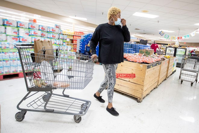 Natangi Griffin adjusts her mask as she pulls her cart through the produce department while grocery shopping Tuesday, May 19, 2020, at Cash Saver in Memphis.