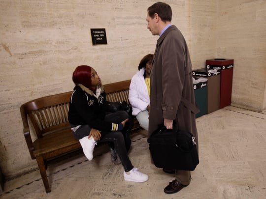 Attorney Jonathan Safran speaks with Sharday Rose, the girlfriend of Derek Williams, at the Milwaukee County Courthouse in 2013 as Williams' grandmother, Ruthie Williams, looks on. Williams died in Milwaukee police custody in 2011.