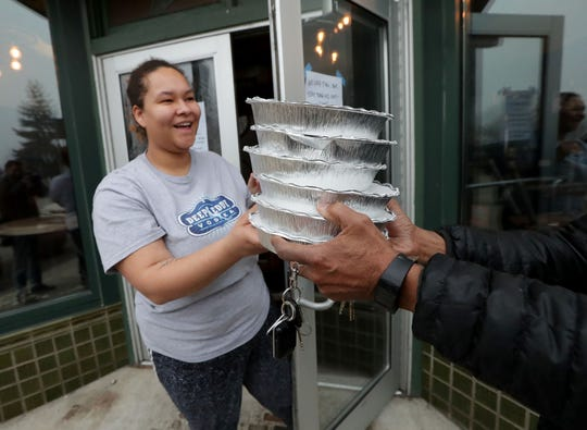 Lydia Phillips, a volunteer for the Tandem, hands out a stack of free community meals.