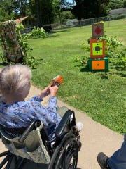 A Lagniappe Healthcare resident enjoys target shooting with a Nerf gun at the facility.