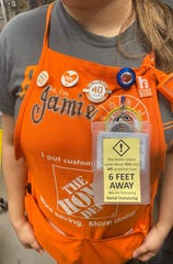 Home Depot employees wear badges to remind customers of social distance guidelines during the coronavirus pandemic.