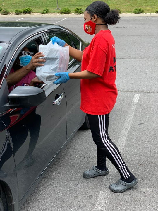 Morgan Lowe takes food out to a customer at Mack's Hot Chicken in Smyrna. Takeout and curbside service is available, and a limited availability for seating inside.