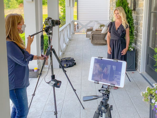 Using social distancing and a mask during taping for a video series, videographer Geinger Hill captures Realtor Marabeth Poole on a porch of a LCT Team - Parks listing at 1401 Montmorenci Pass in Brentwood.