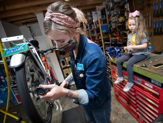 Taylor Kehrer repairs a bike at Green Fleet Bicycle Shop as her daughter Taylor Coppage, 6, watches in the background Wednesday, May 20, 2020 in Nashville, Tenn.