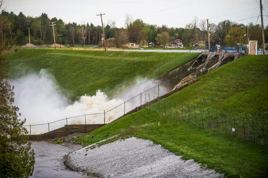 Water rushes through the Edenville Dam, Tuesday, May 19, 2020 in Edenville, Mich. People living along two mid-Michigan lakes and parts of a river have been evacuated following several days of heavy rain that produced flooding and put pressure on dams in the area. (Katy Kildee/Midland Daily News via AP)