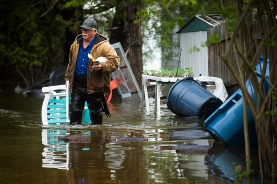 Mark Musselman brings a chair to the front of his house from the back yard, wading through floodwater, Tuesday, May 19, 2020 in Edenville, Mich. People living along two mid-Michigan lakes and parts of a river have been evacuated following several days of heavy rain that produced flooding and put pressure on dams in the area. (Katy Kildee/Midland Daily News via AP)