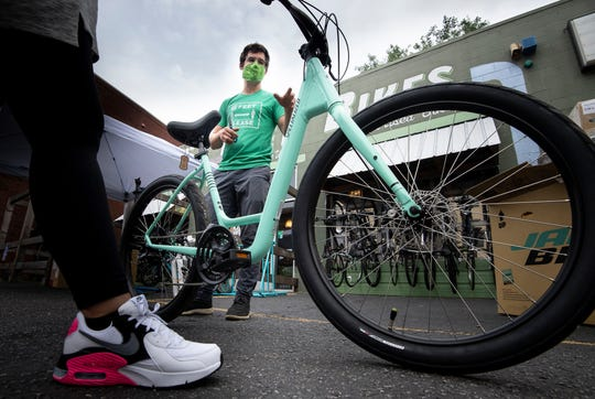 Austin Bauman, owner of Green Fleet Bicycle Shop, demonstrates a new bike to a customer at his shop on Jefferson Street on Wednesday, May 20, 2020 in Nashville, Tenn.