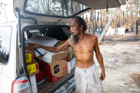 Khamdy Kiewsida keeps his belonging safe inside his car as pictured, Tuesday, May 19, 2020, at his home in Golden Gate Estates. Kiewsida has refused to take shelter at a hotel and has remained on his property since the fire destroyed him.