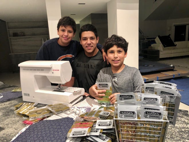 From left to right: Diego, Max and Nicolas Bazan all volunteer their time to make masks.