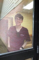 Newark senior Nick Summers was photographed by his mother through the glass while working at the Inn at SharonBrooke,  during a 65-day quarantine at the assisted living facility.