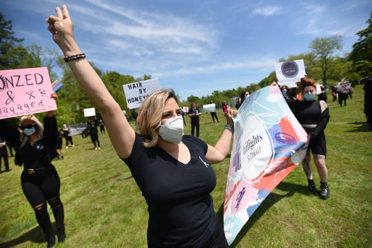 Tricia DiFranco, C , owner of Hilights Salon in Lyndhurst, the leader of the NJ Salon and Spa Coalition on Facebook, shows her placard together with other members as they gather peacefully at Verona Park in Verona on 05/20/20.