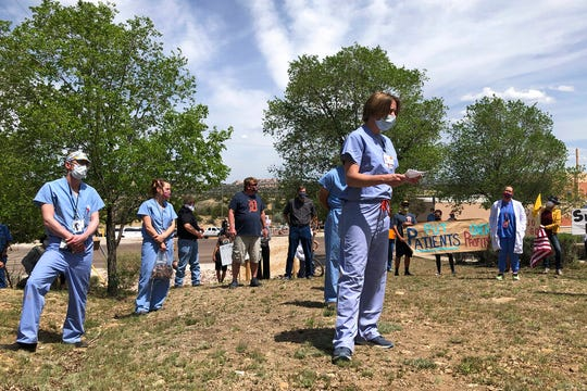 In this photo taken May 8, 2020, medical staff from Rehoboth McKinley Christian Hospital including Chief Medical Officer Val Wangler, center, hold a protest over working conditions and depleted staff in Gallup, N.M. Many nurses and doctors say staffing at the hospital was inadequate because of hospital CEO David Conejo's move to cut back on nurses in the first week of March to offset declining hospital revenues after elective surgeries were suspended. They voiced their discontent at the recent protest calling for his resignation.