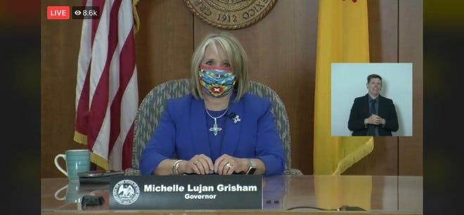 New Mexico Gov. Michelle Lujan Grisham, wearing a cloth mask, opens a virtual news conference from the state Capitol building in Santa Fe on Wednesday, May 20, 2020.