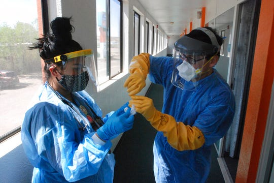 In this May 7, 2020, file photo, Certified Medical Assistant Shaniya Wood, left, and physician Caleb Lauber, right, test one of over 100 homeless patients who were being isolated in motels for the coronavirus in Gallup, N.M.