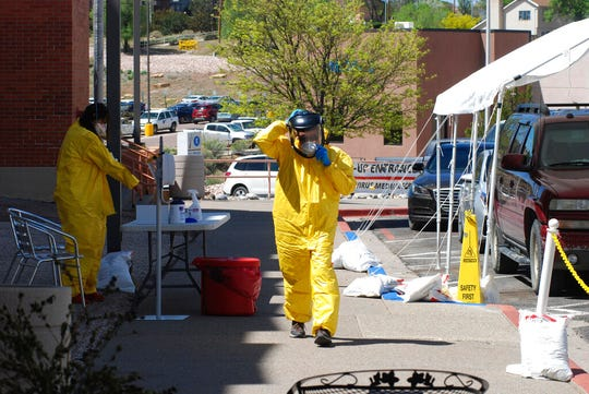In this May 7, 2020, photo, medical staff from Rehoboth McKinley Christian Hospital put on protective equipment as they work at a drive-thru coronavirus testing site outside the hospital in Gallup, N.M. Of about 500 medical and support staff, at least 32 hospital workers have become infected, and doctors and nurses say that they all live with the fear of spreading the virus to their colleagues and relatives.