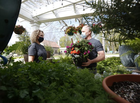 Sherry Klemp, of Winneconne, talks with House of Flowers owner Jim Kolb on Wednesday at the Oshkosh business. The floral store recently reopened after the Supreme Court struck down the state's safer-at-home order due to the coronavirus pandemic.