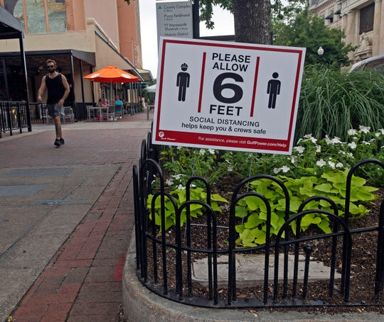 Signs in downtown Pensacola on Wednesday remind visitors to practice social distancing and remain at least six feet apart during the coronavirus pandemic.