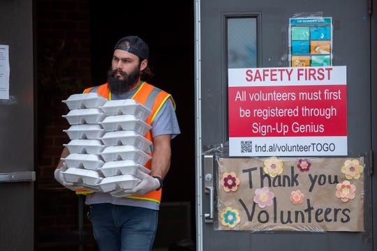 Un voluntario de Red Door Food Pantry distribuye comidas calientes a familias afectadas por la pandemia de coronavirus, en Cartersville, Georgia, EE. UU., 30 de abril de 2020.