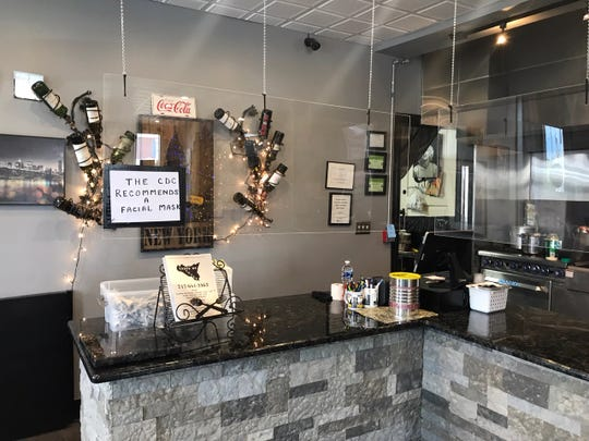 Taste of Sicily hung plexiglass around their counter, with a sign reminding customers that the CDC recommends wearing a face mask.