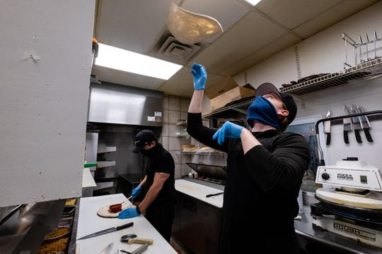 Chad Cartmell works on preparing a pizza in the kitchen of Casey's Tuesday, May 19, 2020, in Port Huron. Cartmell has worked over 60 consecutive days during the pandemic, and isn't taking a day off until the restaurant is closed Sunday for Memorial Day weekend.